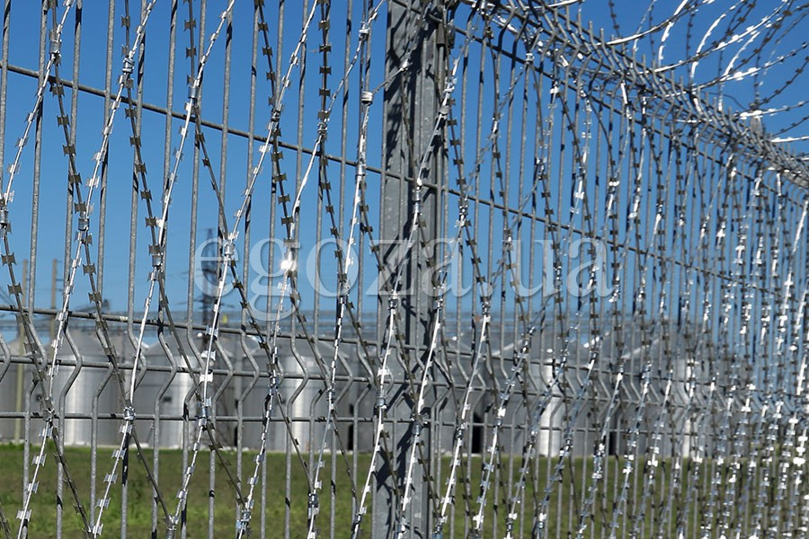 Fence of welded panels and barbed wire mesh