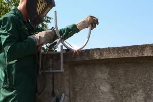 Монтаж кронштейна на паркан з бетонних плит